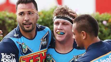 Ryan James, Jarrod Wallace and Phillip Sami of the Titans celebrate a try.