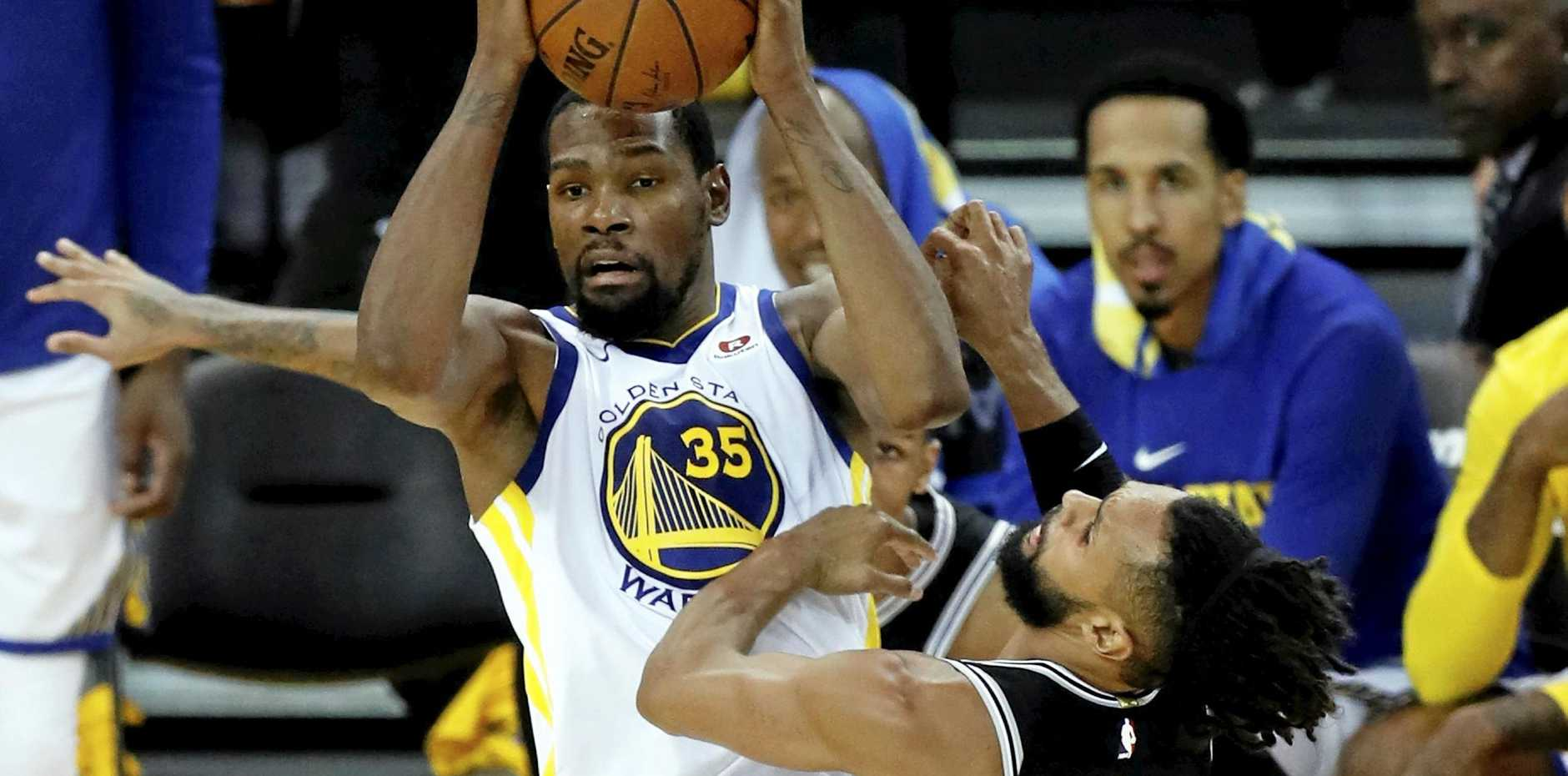Golden State forward Kevin Durant looks to pass as he gets some attention from San Antonio Spurs guard Patty Mills in the fifth game of their NBA playoff series on Wednesday, April 25 (AEST).
