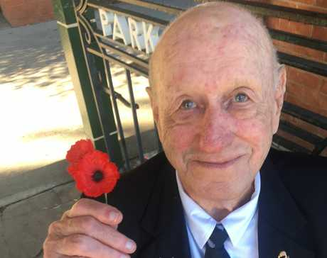 Sid Porter helps hand out poppies before the march begins at Grafton