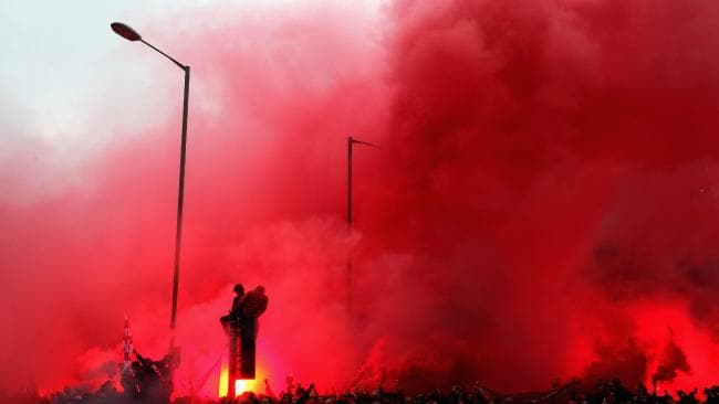 Liverpool fans light flares outside the stadium.