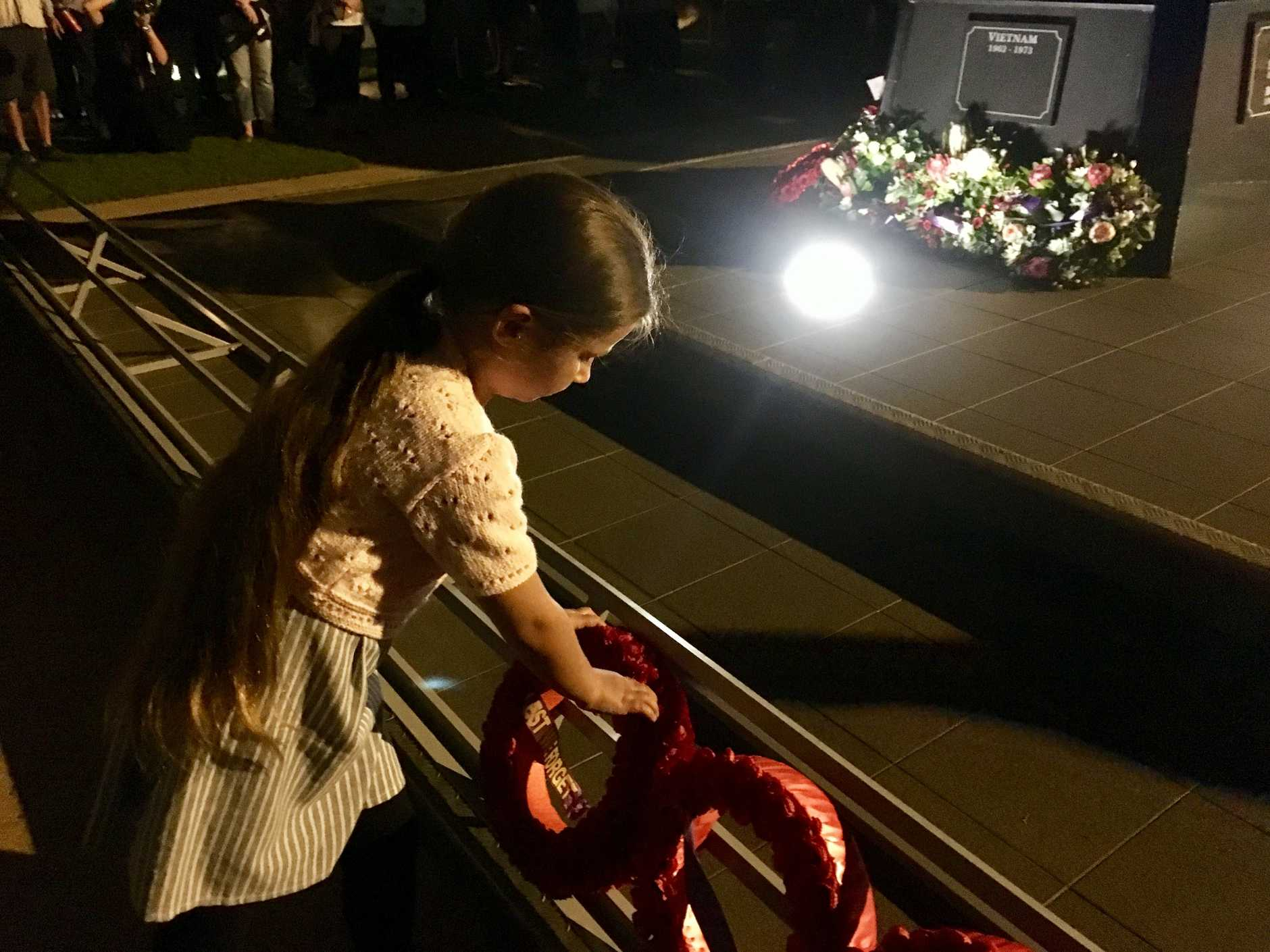 Isabella Storer, 7, of Sippy Downs lays a wreath at the Cotton Tree Dawn Anzac Day service.