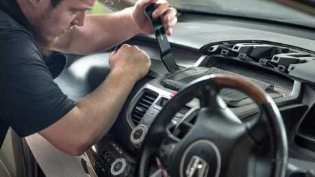 A technician disassembles part of the dashboard to get access to the passenger airbag in a Honda. Picture: Supplied.