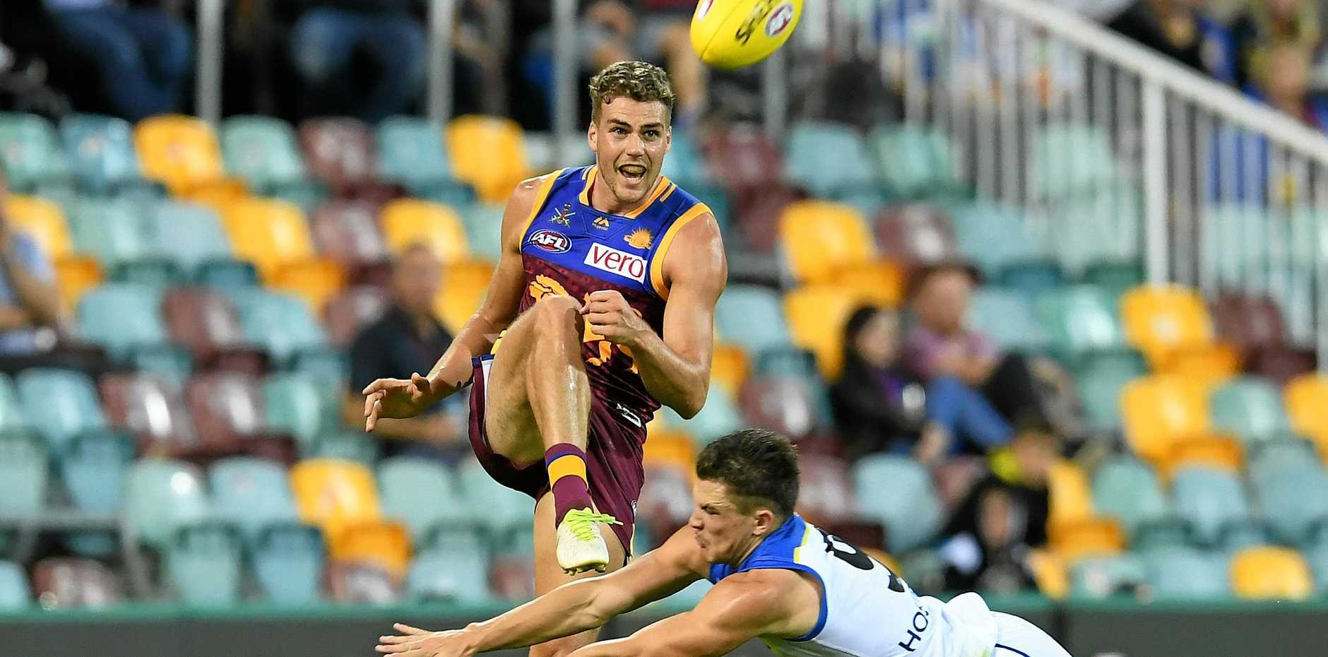 The Lions' Tom Cutler gets his kick away despite the efforts of the Suns' Ben Ainsworth during their teams' round five clash at the Gabba last Sunday. Picture: Dan Peled/AAP