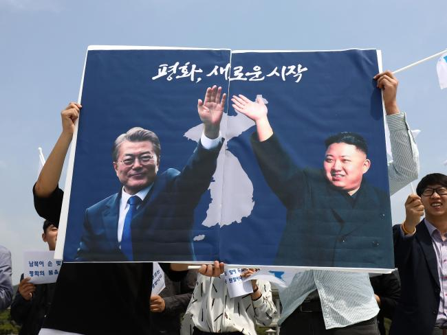 South Koreans hold up placards of President Moon Jae-In and North Korean leader Kim Jong-un during a rally welcoming the planned Inter Korean Summit. Picture: Chung Sung-Jun/Getty Images