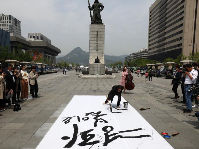 People in Seoul write goodwill messages during their rally welcoming the planned inter Korean Summit. Picture: Chung Sung-Jun/Getty Images