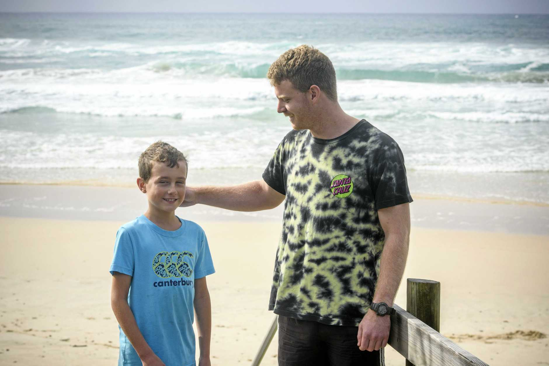 Robert Miller, 9, is reunited with one of his rescuers Jake Scobie, after he was caught in a rip on Pippi Beach this week