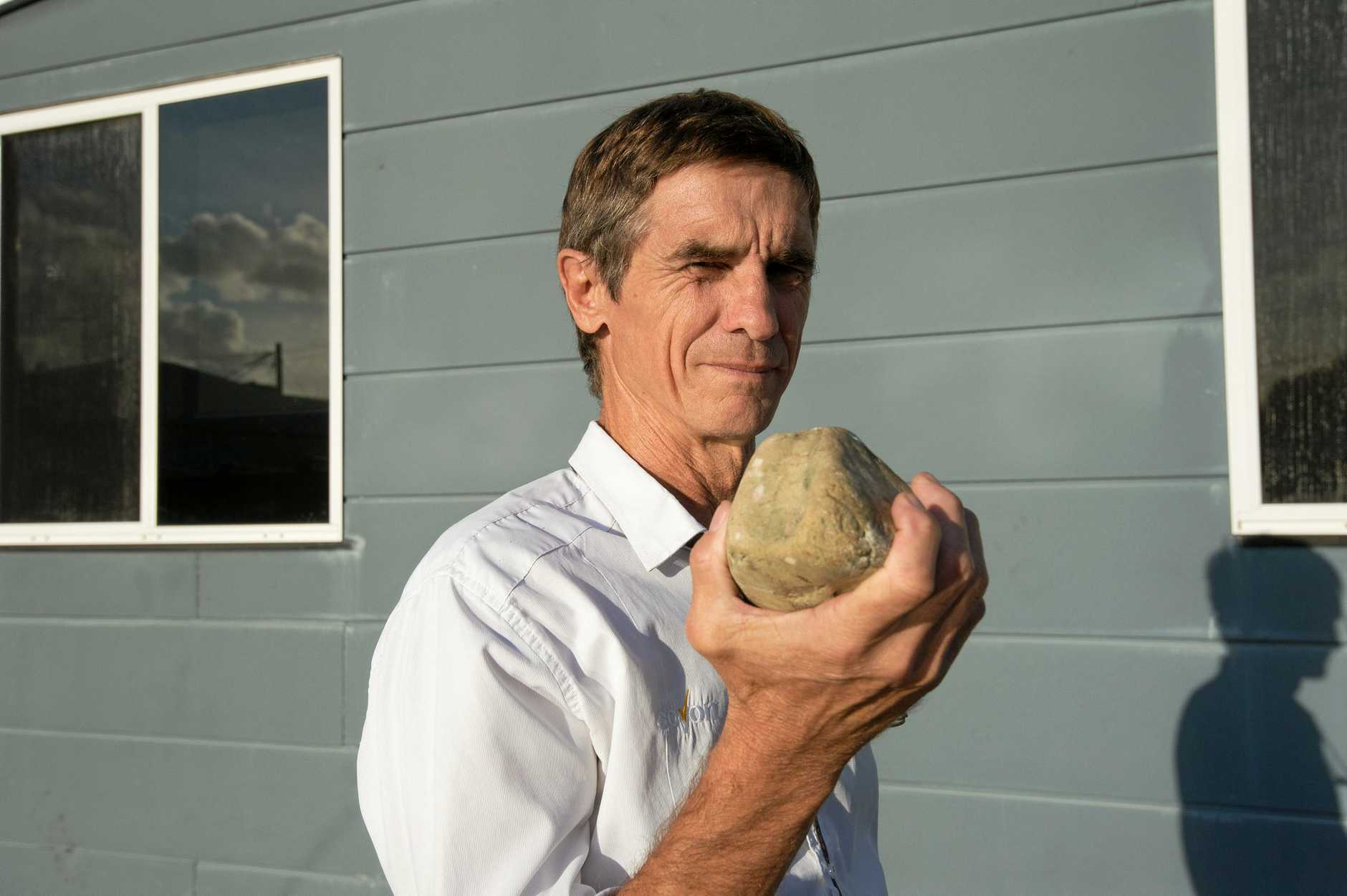 Brian Hopwood with the rock used to damage his premises. 01 MAY 2018