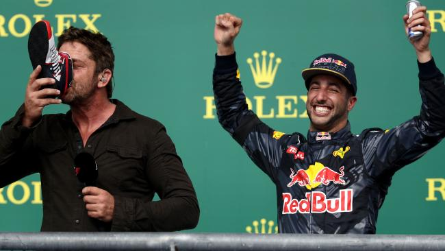 Actor Gerard Butler, with Daniel Ricciardo to his right, was an early victim of the Shoey. Picture: AFP