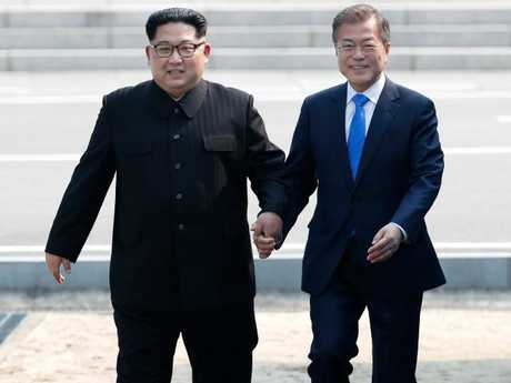 The beaming Korean leaders holding hands in the DMZ has raised hopes there will be peace on the peninsula at last. Picture: Korea Summit Press Pool/AP