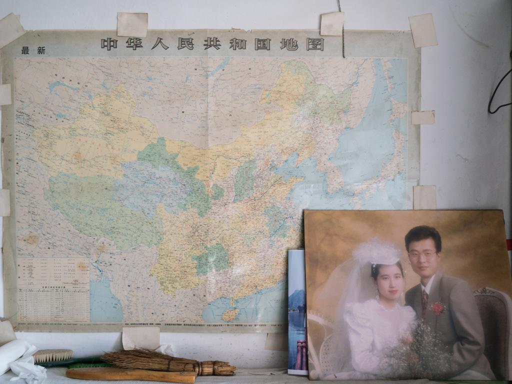 Han Zicheng had a wedding photo of his estranged son hanging in his room. They lived in Canada and were unable to visit him. (Photo by Yan Cong for The Washington Post via Getty Images)