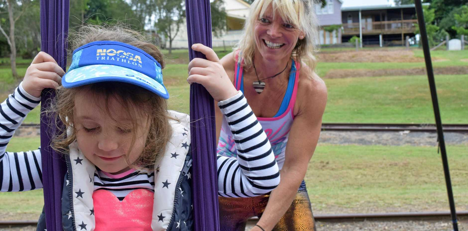 Carinne Kempler gives a helpful push to Jessica Robey, of Imbil, as she tried out the aerial silks acrobatic venue at Imbil's Labour Day celebrations.