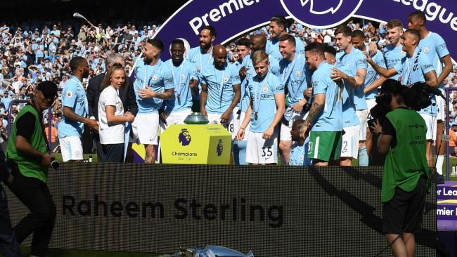 The Premier League trophy falls onto the pitch as Manchester City players celebrate