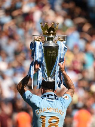 Manchester City's English defender Kyle Walker holds the Premier League trophy on the pitch