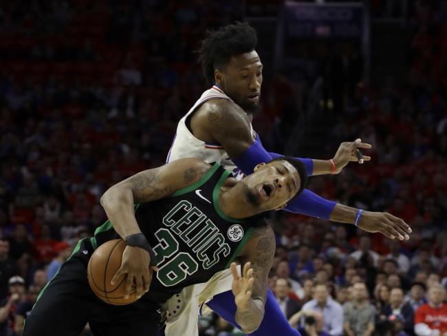 Boston Celtics' Marcus Smart goes down under pressure from Philadelphia 76ers' Robert Covington.