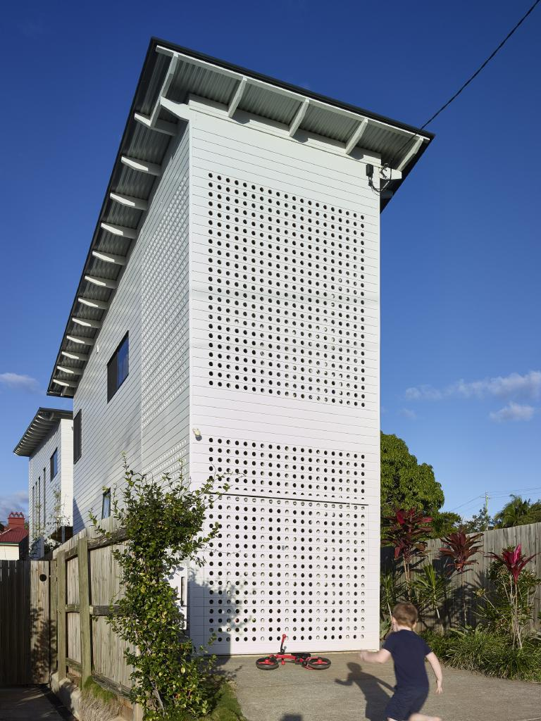 STREET FRONT: The perforated screen extends up to the roof, and disguises the carport and creates privacy for the deck above. Designers: Kirsty Volz and David Toussaint Builder: Thallon and Mole Photography: Scott Burrows
