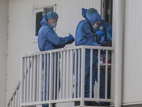 Forensics teams collect evidence from the top floor of the apartment block. Picture: David Martinelli