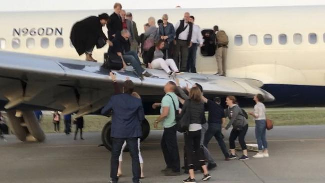 Passengers stand on the tarmac of Denver International Airport after being evacuated from a Delta flight from Detroit in Denver. Picture: AP