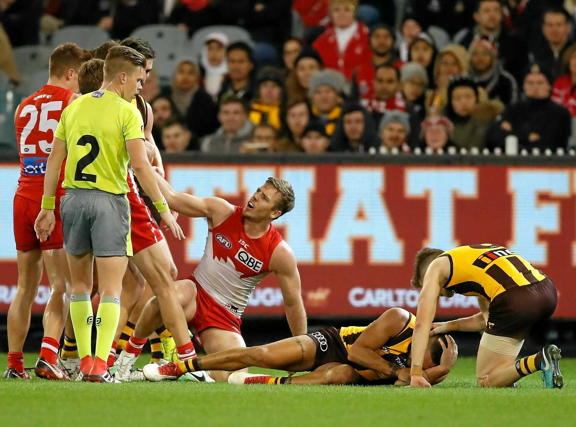Jarman Impey lies prostrate on the ground as the Swans' Luke Parker denies any intent.