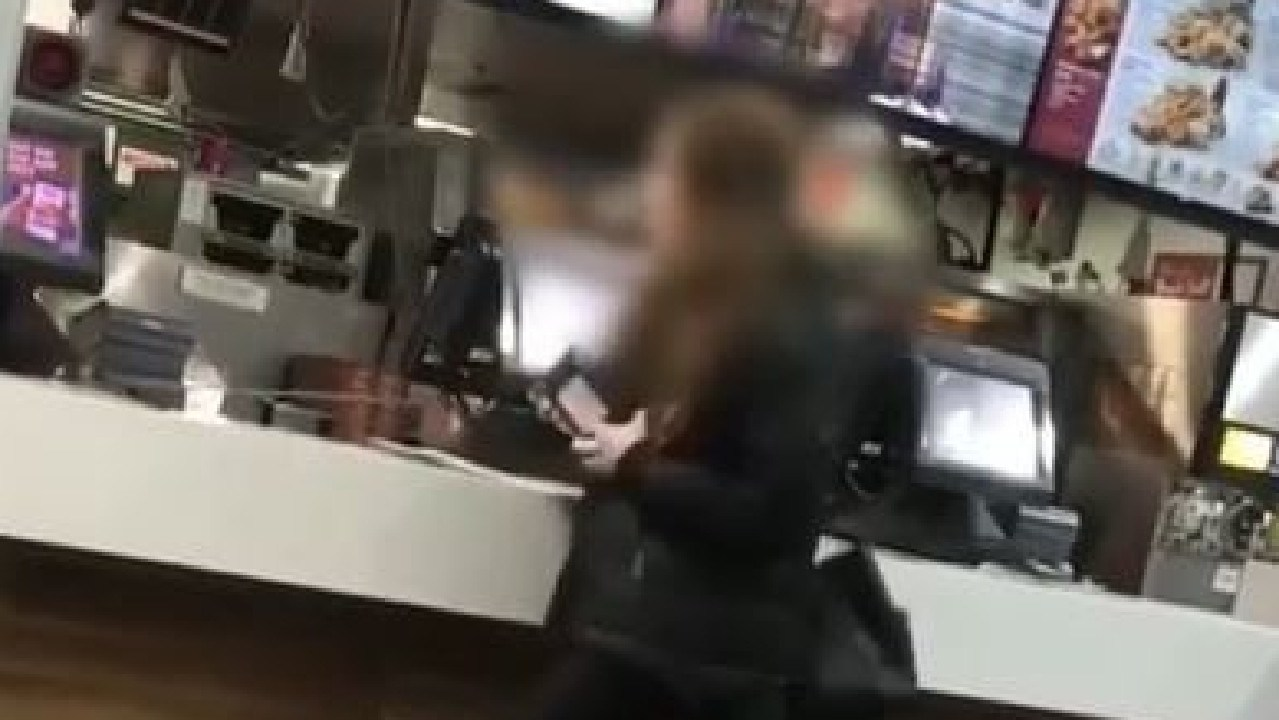 The woman yanks an EFTPOS machine off the counter during the rampage, which reportedly took place at KFC on Hindley St. Video @YeahCeebs/@ShitAdelaide