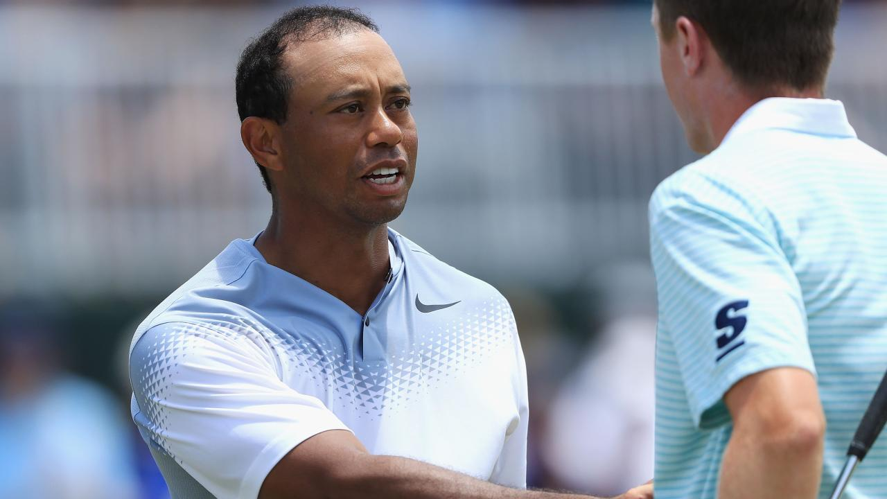 Tiger Woods shakes hands with Mackenzie Hughes after finishing on the 18th green.