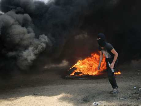 A Palestinian man walks in the smoke billowing from burning tyres during clashes with Israeli forces along the border with the Gaza strip. Picture: AFP