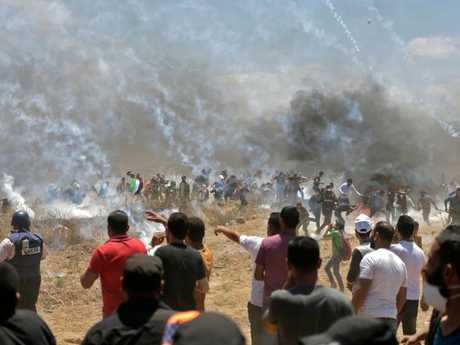 Palestinian protesters run for cover from tear gas during clashes with Israeli forces near the border between the Gaza strip and Israel east of Gaza City. Picture: AFP