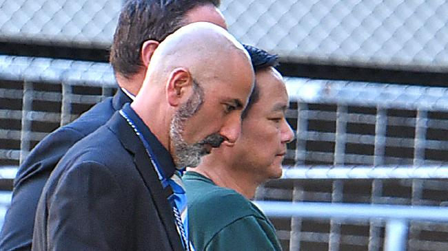 Police escort Zhen Jie Zhang to the Gold Coast police lock up after he was extradited from Grafton. Picture: AAP image, John Gass
