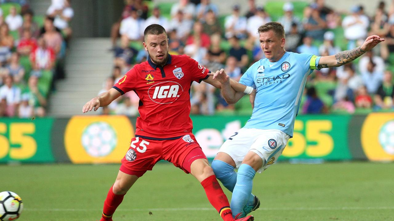 Michael Jakobsen contests with Apostolos Stamatelopoulos of Adelaide United.