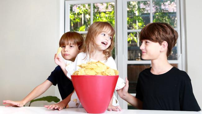 Jack, 10, Elliott, 6 and Holly, 3 eat chips that were advertised as a different weight to what they actually were. Picture: AAP/Image Sarah Marshall