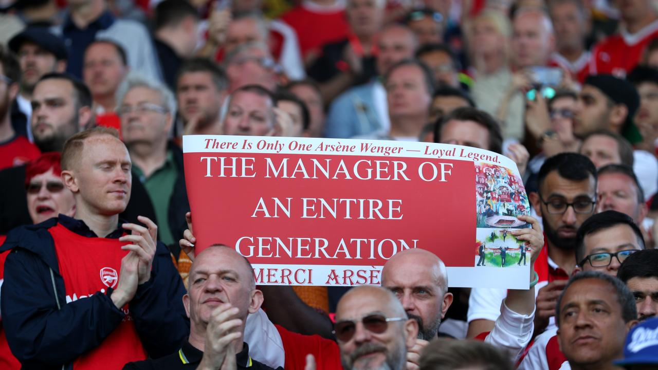 Fans hold a sign as a tribute to Arsene Wenger