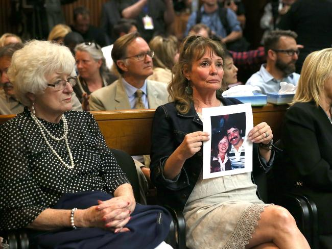 An attendee holds a photo of Cheri Domingo and her boyfriend Gregory Sanchez, who were killed in 1981, as she sits in the courtroom during the arraignment of Joseph James DeAngelo, the suspected 'Golden State Killer'. Picture: AFP