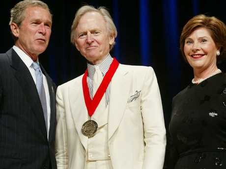 Then US President George W Bush, left, poses with author Tom Wolfe, centre, and first lady Laura Bush in 2002 as the author received the National Humanities Medal. Picture:  AP