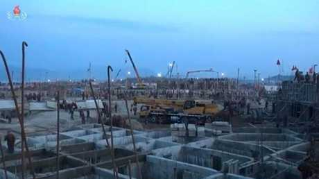 Photos from the ground show floodlights erected along the coast so construction can continue at night.