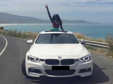 One of South Sudanese General James Hoth Mai's daughters on a stretch of Australian coastline in a BMW.