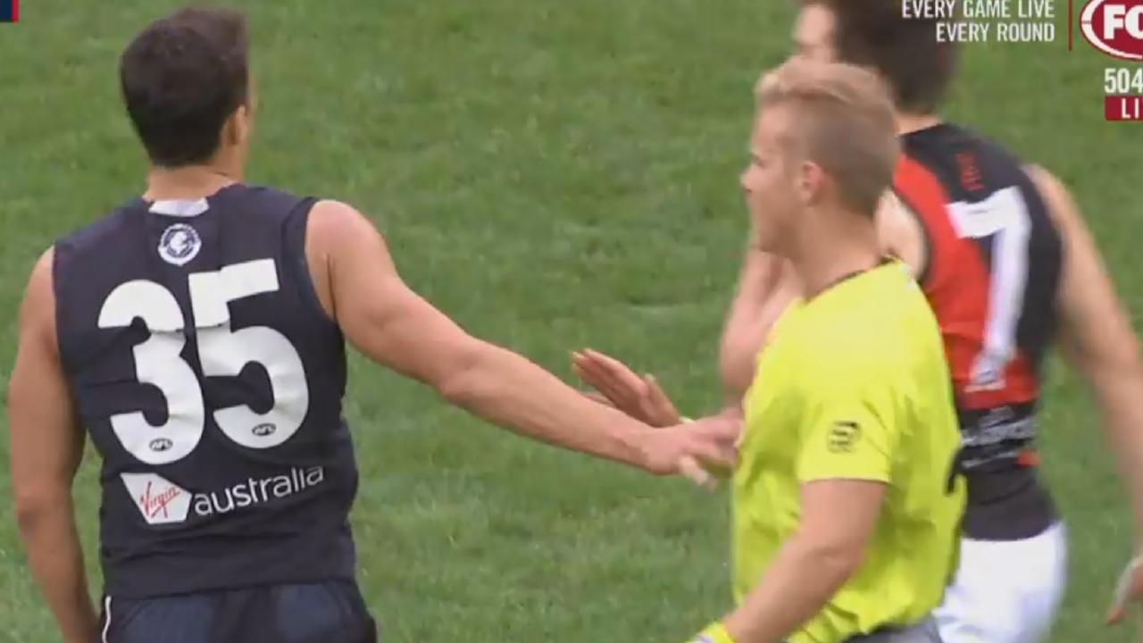 Ed Curnow places his hand on the chest of an umpire. Picture: Screen shot