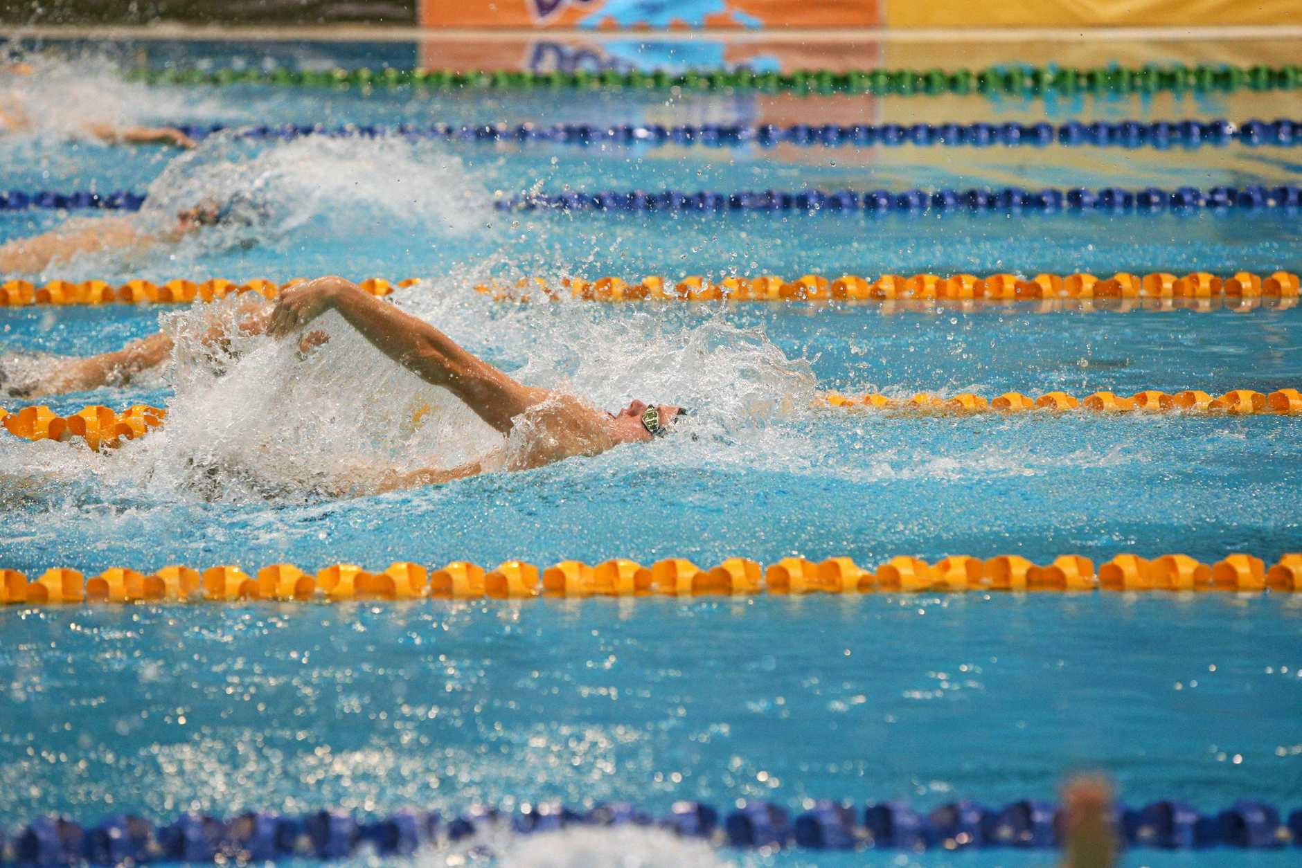 SWIM STAR: Ty Hartwell powers to victory in the 200m backstroke at the Georgina Hope Foundation Australian Age Championships in Sydney and (right) with his gold medal.