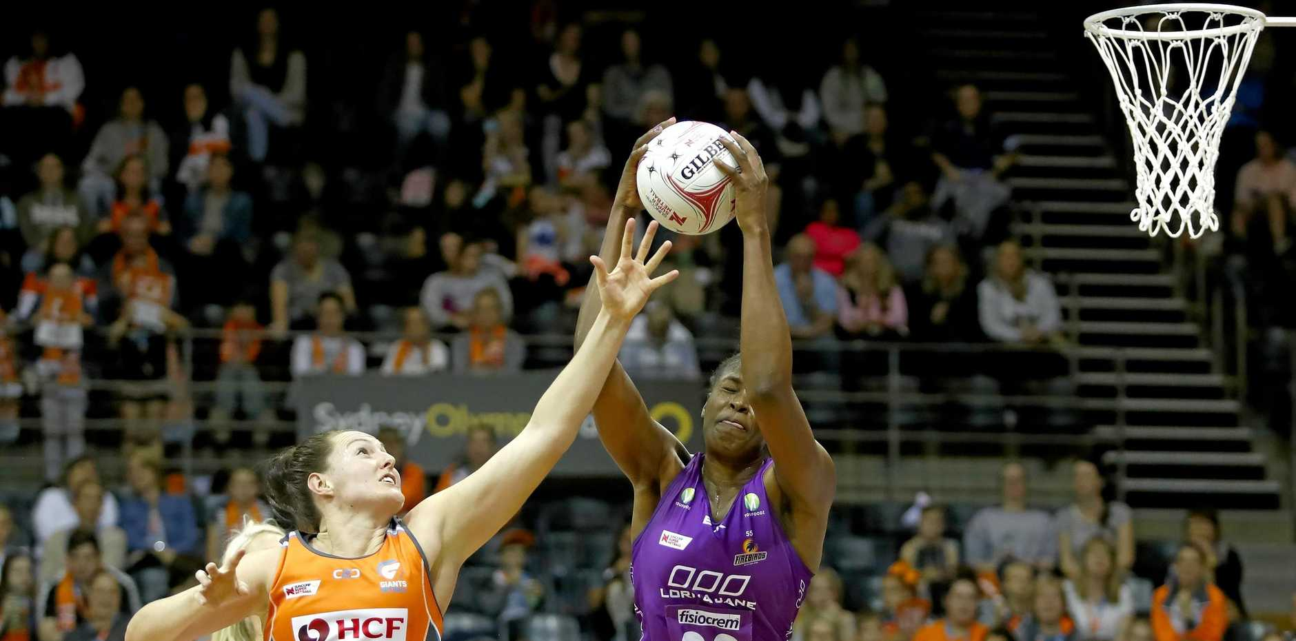 Romelda Aiken of the Firebirds gets possession despite the efforts of the Giants' Samantha Poolman in their Super Netball match on Saturday.