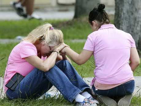 Two women console each other near the high school. Picture: Jennifer Reynolds /The Galveston County Daily News via AP