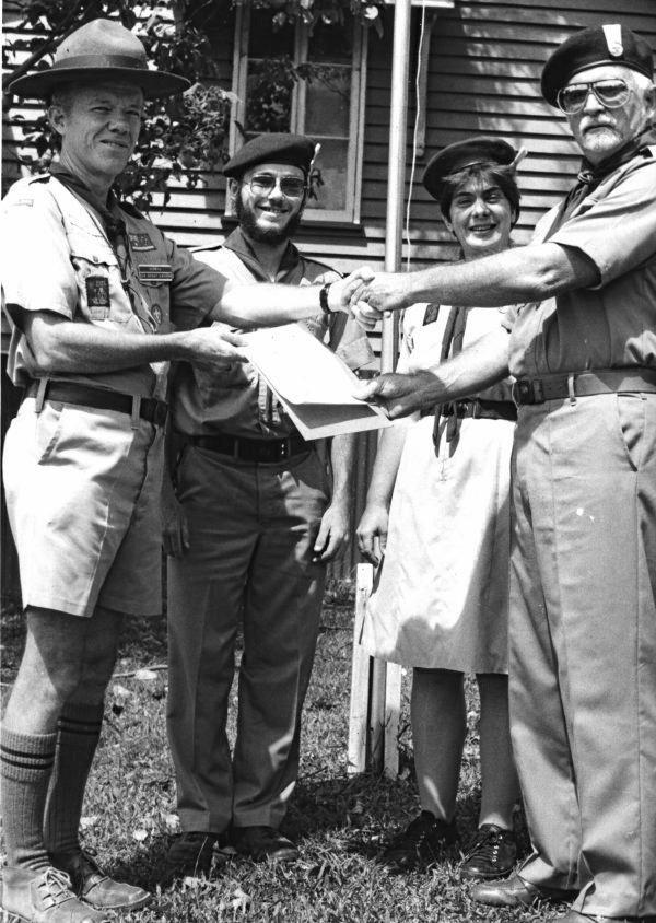 Dudley Tate (left) receives the Australian Scout Association's special Long Service Award in 1988 from Group Leader Hugh Milne while Mr Tate's assistant leaders.