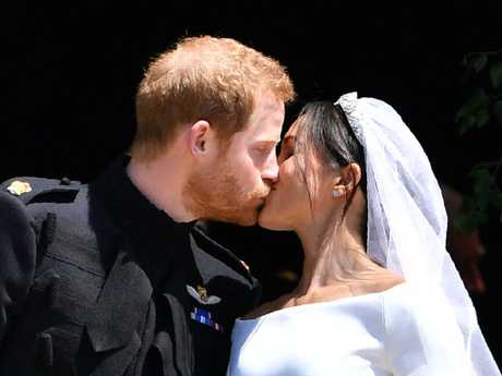 TOPSHOT - Britain's Prince Harry, Duke of Sussex kisses his wife Meghan, Duchess of Sussex as they leave from the West Door of St George's Chapel, Windsor Castle, in Windsor, on May 19, 2018 after their wedding ceremony. / AFP PHOTO / POOL / Ben STANSALL