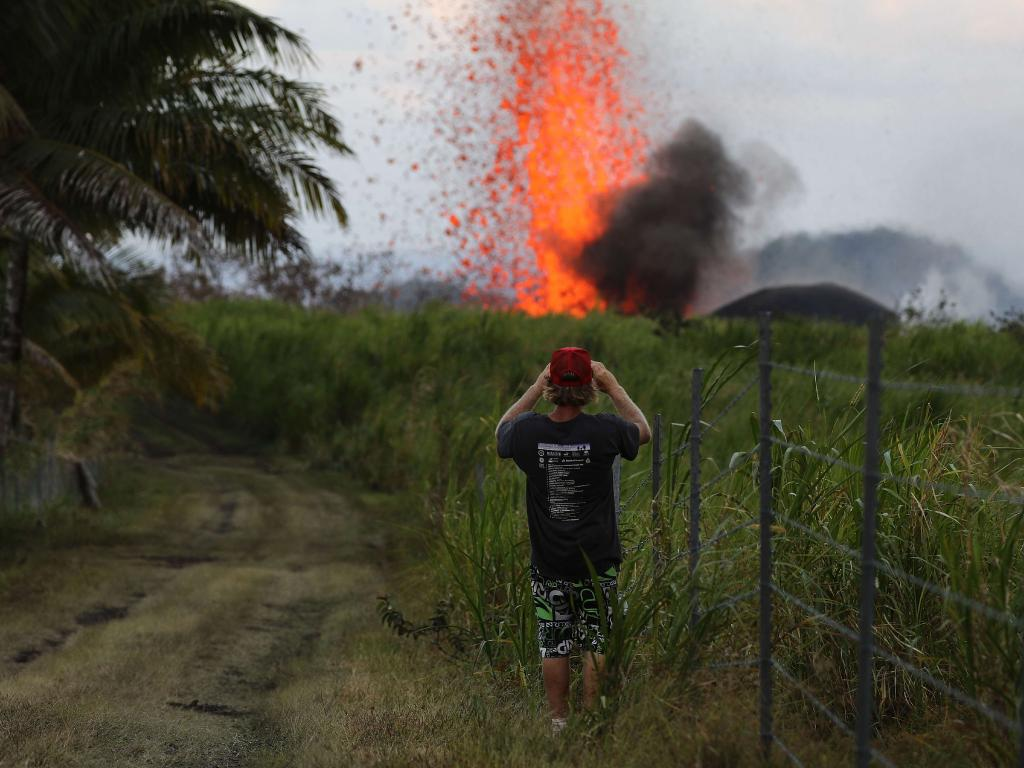 A man takes a photo of a lava fountain from a Kilauea volcano fissure on Hawaii's Big Island. Mario Tama/Getty Images/AFP
