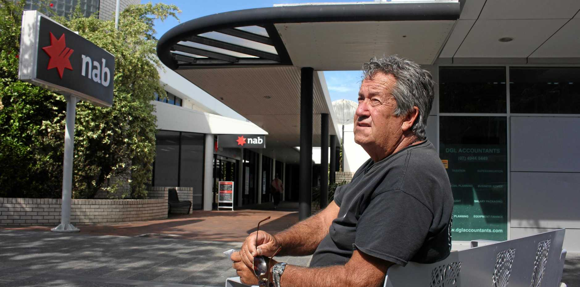 Robin Moore, back in Mackay, sitting outside the NAB Bank where he was allegedly king hit two years ago.