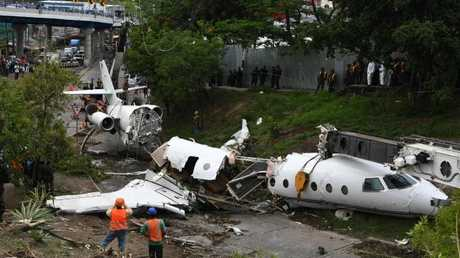 Firefighters and rescue personnel work at the site of an accident, after a plane went off the runway at Toncontin International airport and collapsed over a busy boulevard in Tegucigalpa on May 22, 2018. Picture: AFP / Orlando Sierra.