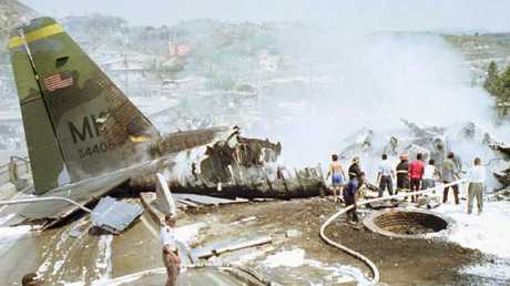 Rescue workers inspect the wreckage of a US military cargo plane which crashed and caught fire on a city street, April 1, 1997 while trying to land to the Toncontin International Airport in Tegucigalpa, Honduras. Picture: AP /Eugene Hoshiko.