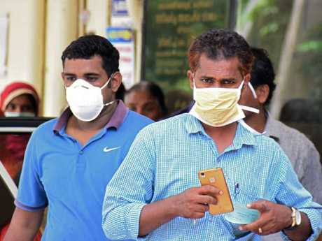 Indian residents wear face mask outside the Medical College hospital in Kozhikode on May 21, 2018. A deadly virus carried mainly by fruit bats has killed at least three people in southern India, sparking a statewide health alert May 21. Eight other deaths in the state of Kerala are being investigated for possible links to the Nipah virus, which has a 70 percent mortality rate. / AFP PHOTO / -