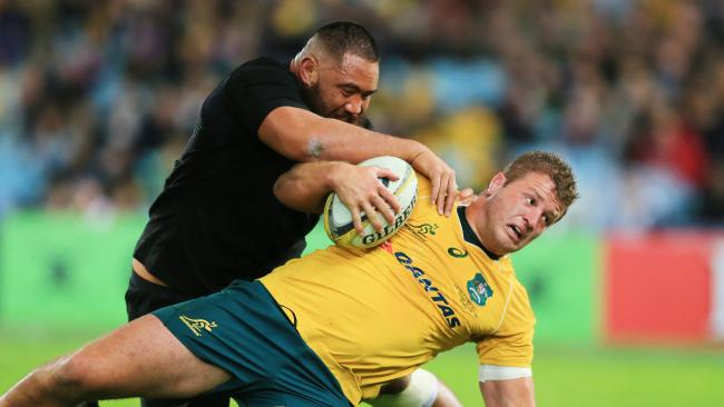 James Slipper of the Wallabies is tackled by All Blacks rival Charlie Faumuina.