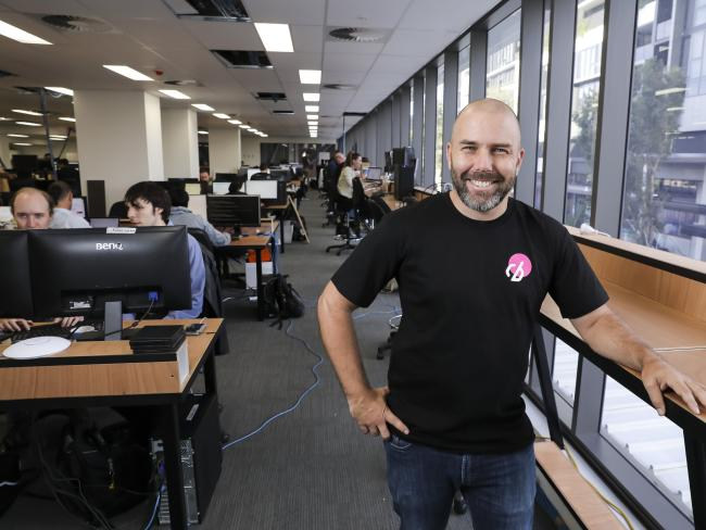 Eban Escott's Milton-based business is booming. He has robots that write code for robots. Picture: Mark Cranitch