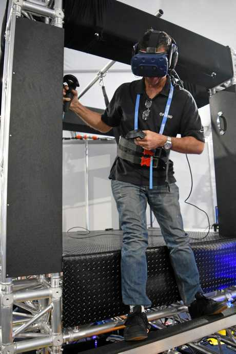 Research and development worker Gavin Broadley tries a helicopter simulator designed on the Sunshine Coast to give cabin crew a virtual reality flight experience.