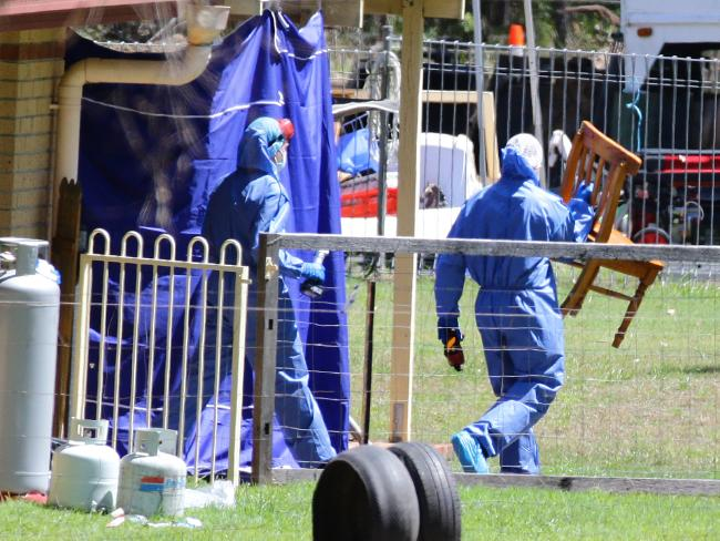 Police remove a chair from the Thorburns' Chambers Flat house. Picture: Darren England