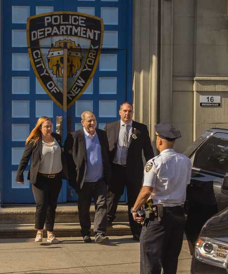 Harvey Weinstein, middle, is loaded into an unmarked vehicle while leaving the first precinct of the New York City Police Department after turning himself to authorities following sexual misconduct allegations.